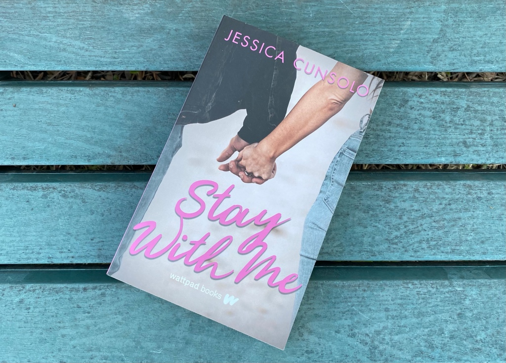 """Book cover of a boy and girl holding hands with pink text with the words """"Jessica Cunsolo"""" and """"Stay with Me"""" along with """"Wattpad Books"""" on a light blue wood background"""