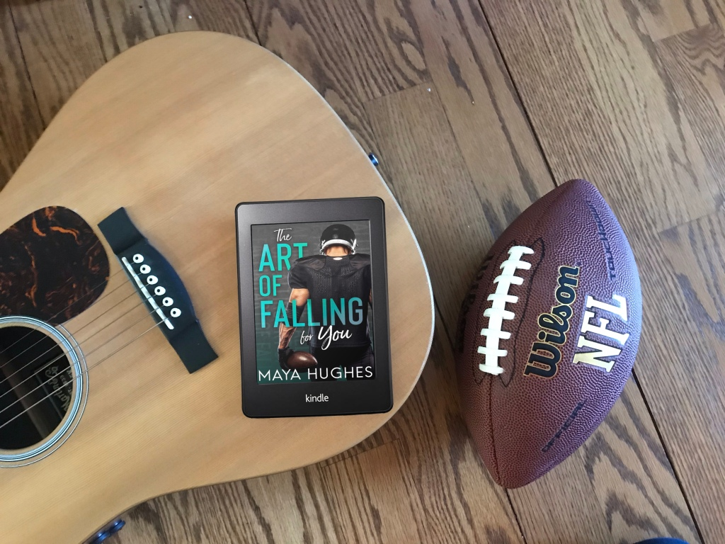 "A kindle with the cover art of ""The Art of Falling for You"" on top of an acoustic guitar, with a football on the hardwood floor next to it."